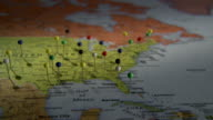 CU Human hand placing push pin in map of North America / Atlanta, Georgia, USA