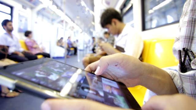 Human Hand playing Digital Tablet on the sky train