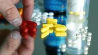 Human Hand Selecting Medication Pills & Capsules