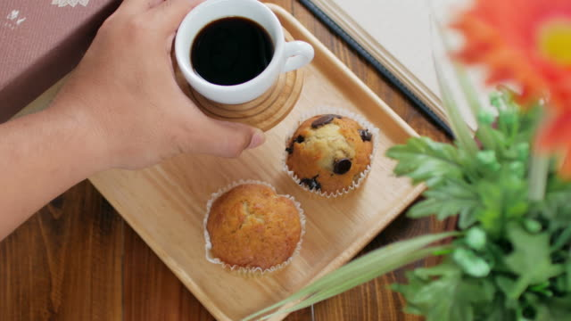 Human hand Setting breakfast set muffin cake and gen serial food with black coffee , dolly shot right to left
