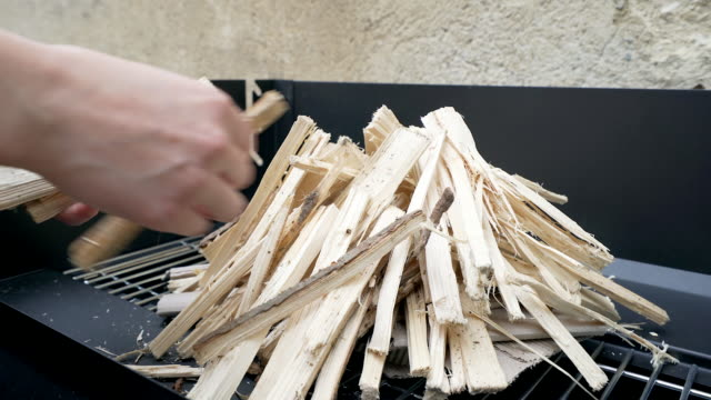 Human hands preparing firewood for a barbeque.