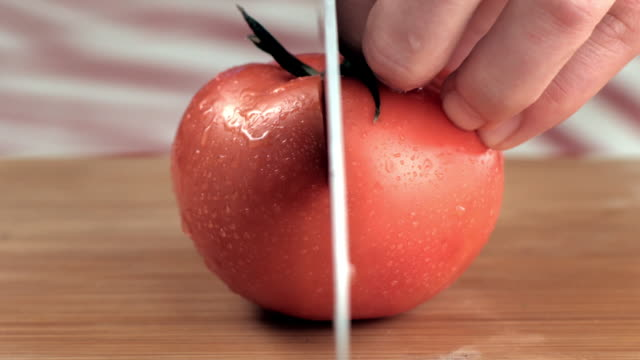 Human hands slicing tomato with knife