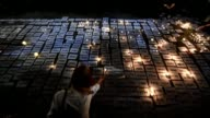 Human rights activists light candles over numbered place cards on the eve of the 20th anniversary of the Srebrenica massacre in Belgrade