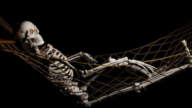 Human skeleton swingig on hammock