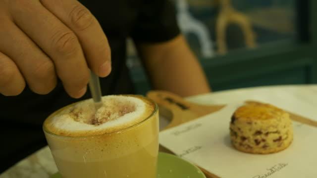 human's hand stirring sugar in coffee cup
