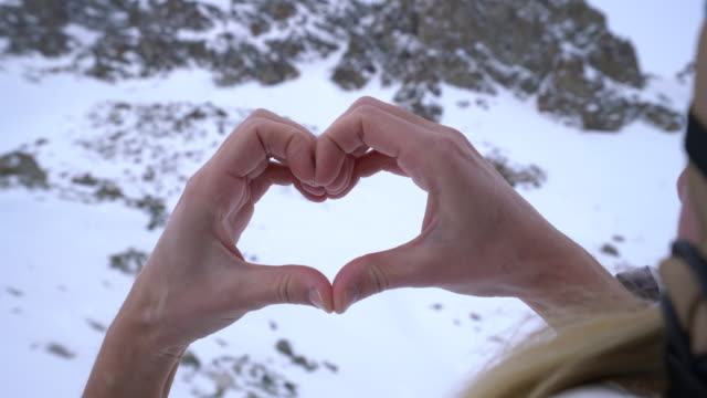 Human's hands making heart shape on snowy mountains landscape