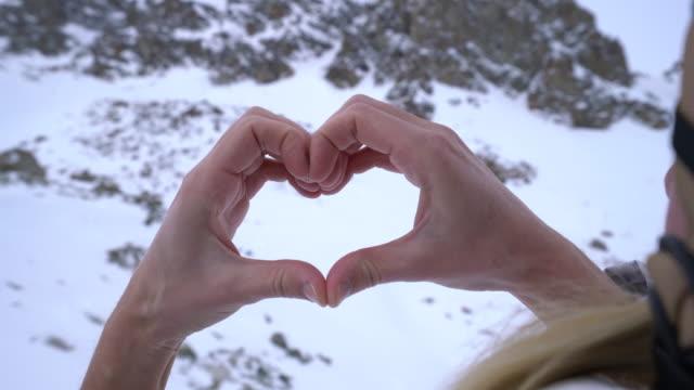 Human's hands making heart shape on snowy mountains landscape