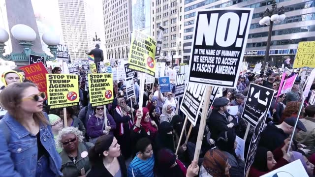 Hundreds gathered at Federal Plaza hold placards as they stage a protest against President Trump on the onemonth anniversary of his inauguration in...