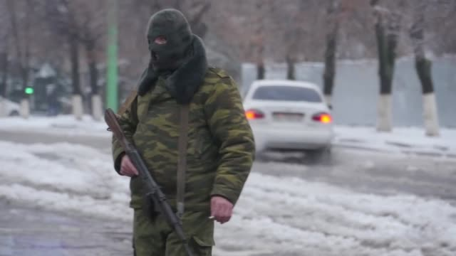 Hundreds of armed men in military fatigues on Tuesday blocked access to government buildings in eastern Ukraine's rebel held Lugansk as infighting...