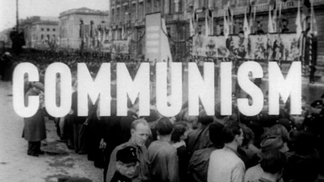 Hundreds of communist protesters all wearing the same uniform of shirts and shorts holding flags signs and clapping hands / demonstrators walk past...