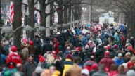 Hundreds of Donald Trump supporters engage in a running stampede on a sidewalk near the intersection of 9th and Pennsylvania Avenue to see their...