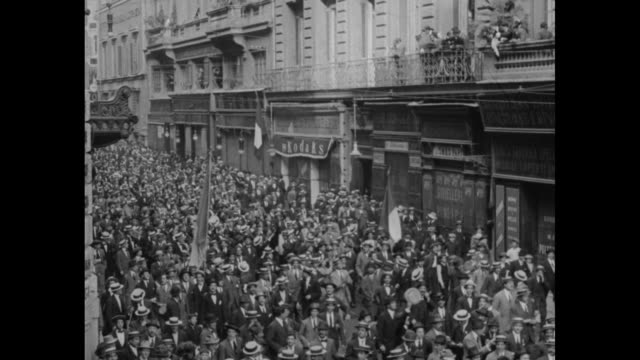 Hundreds of men on Rome street with others on balcony waving handkerchiefs the crowd stopped at columned ministry building to indicate support of...