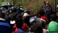 Hundreds of mostly Syrian refugees forced their way over the Macedonian border Saturday as police hurled stun grenades in a failed bid to stop them...