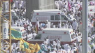 Hundreds of pedestrians make their way around ambulances that inch slowly through the crowd in Saudi Arabia.