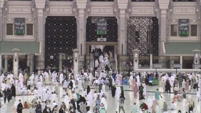 Hundreds of pilgrims and visitors walk in front of the Grand Mosque.