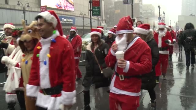 Hundreds of revelers parade through the streets of New York dressed as Santa and his elves for the city's annual celebration of Santa Con