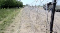 Hungarian soldiers on Thursday installed the first wires on a controversial fence on the border with Serbia which is aimed at keeping out migrants
