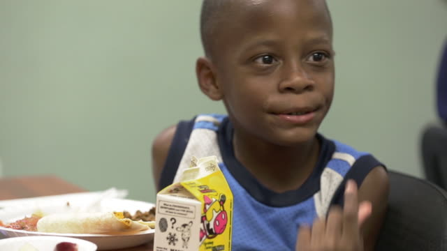 Hungry children eat healthy donated food at a community center