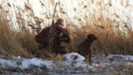 hunter and his dog on the snowy bank of a pond duck hunting