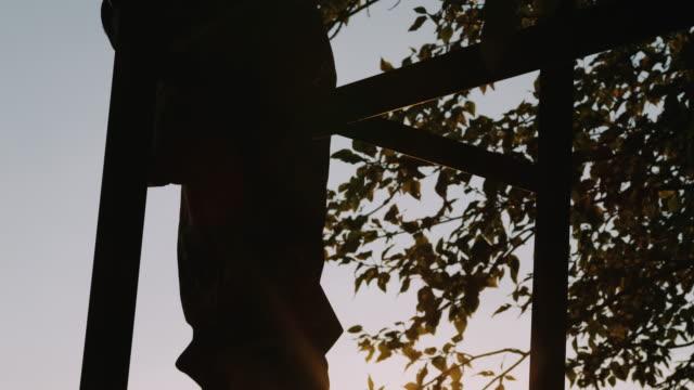 Ein Jäger-Füße sind auf der Leiter der Baumbestand folgte, als er macht sich bereit, in den Abend mit den Sonnenuntergang wunderschön hinter ihm in Zeitlupe zu jagen.