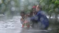Hurricane Harvey now a Tropical Storm returns to land in Louisiana after devastating Texas EXT Various of rescue workers wading through floodwater as...