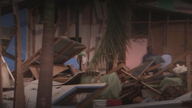 Hurricane Irma clearup operation 2 months on TX Felicito Moses sitting chatting with ITN reporter outside his damaged home