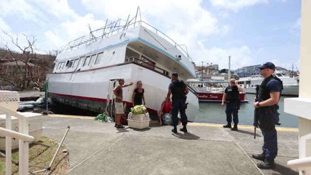 Hurricane Irma evacuees wait around with bags around a boat that has been pushed onto the dock in St John US Virgin Islands on September 12 2017...