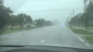Florida Fort Myers Traffic lights blowing in Hurricane Irma wind Stop sign amongst flood water in street Palm trees blowing in wind Street signs in...