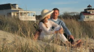 WS PAN Husband and Wife Sitting in Front of Beach House on Dunes / Eastville, Virginia, USA