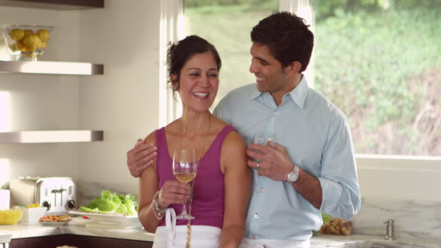 MS Husband kissing wife on cheek while standing at counter in kitchen of contemporary home