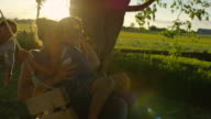 Husband pushing his wife and their little boy on a swing at sunset