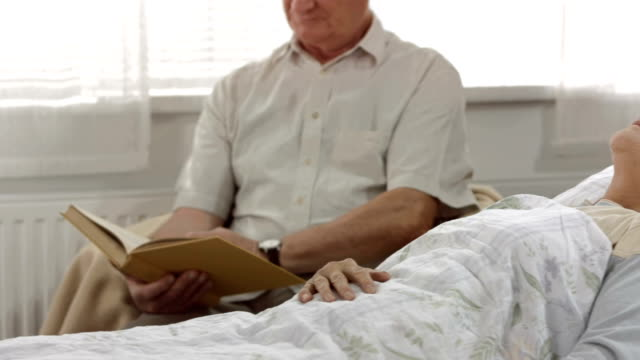HD DOLLY: Husband Reading Beside His Sick Wife