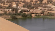Huts populate the shore of a desert lake. Available in HD.