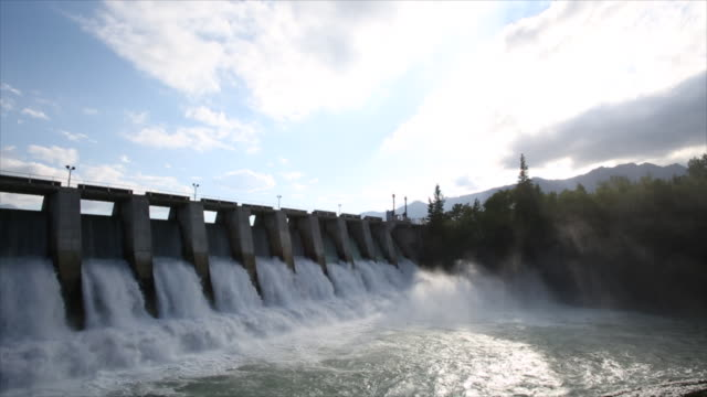 Hydroelectric dam under full river flow, mountains