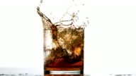 Ice cube falling in whiskey tumbler on white background