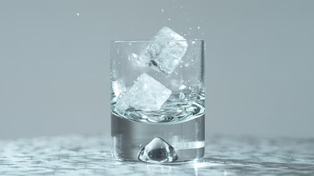 ice cube falls on other ice cube in glass / slow motion