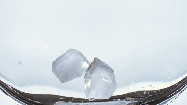CU SLO MO Ice cubes falling into glass against white background / Vieux Pont, Normandy, France