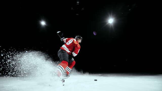 SLO MO Ice hockey player striking the puck