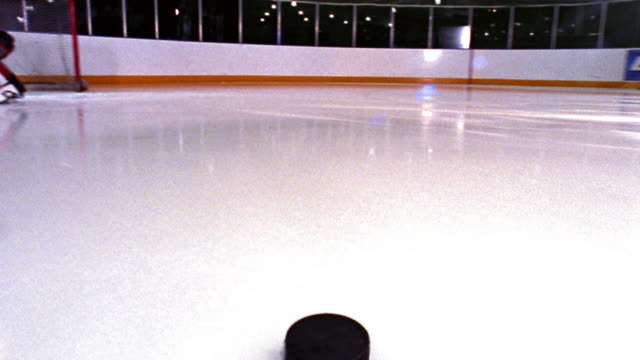 Ice hockey puck point of view across ice, past male goalie + into goal