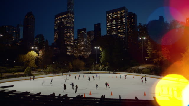 Ice skating in Central Park with Christmas lights in foreground