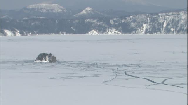 Ice surrounds Kamuishu Island on Lake Mashu in Japan.