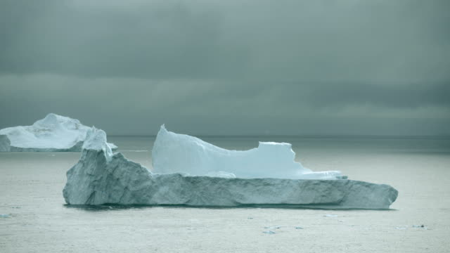 Icebergs Float On Ocean Under Grey Sky