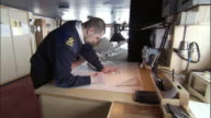 MS, Icebreaker officer in navigation bridge with navigation chart, Russia