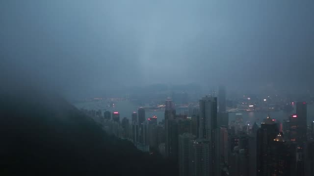 Illuminated buildings stand shrouded in mist as seen from Victoria Peak at dusk in Hong Kong China on Friday Jan 22 2016