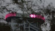 MWS illuminated HSBC logo displayed atop the HSBC HQ building at dusk WS low angle view of illuminated stairwell on the side of the HSBC HQ building...