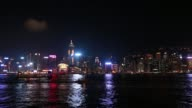 WS Illuminated skyline of Hong Kong Island as a ferry sails along Victoria Harbor on a clear night