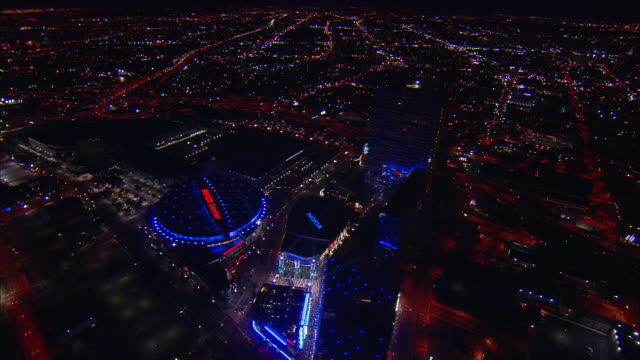 AERIAL Illuminated Staples Center and cityscape at night, Los Angeles, California, USA