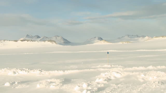 WS TS of Ilyushin Plane coming in to land in snowy windswept landscape, people photographing / Union Glacier, Heritage Range, Ellsworth Mountains, Antarctica
