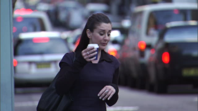 CU, SELECTIVE FOCUS, Impatient woman on busy city street hailing cab, Sydney, Australia