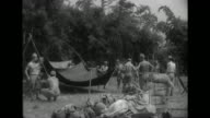 Imperial Japanese Army soldiers set up tents and unload artillery pieces before they clean chickens and cook as they set up a camp